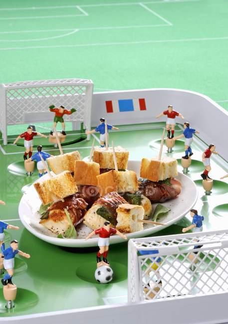 Повышенный вид куриных наггетсов с беконом и шалфеем с футбольными украшениями — стоковое фото