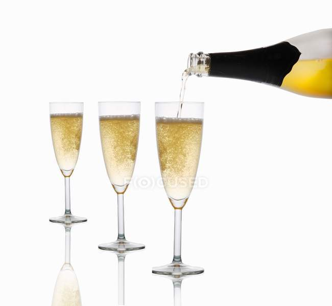 Sparkling wine being poured into glasses — Stock Photo