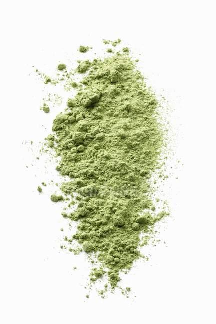 Крупным планом зрения wheatgrass зеленый порошок на белой поверхности — стоковое фото