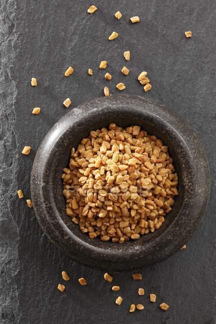 Вид сверху семена пажитника в ступке и на поверхности черный сланец — стоковое фото