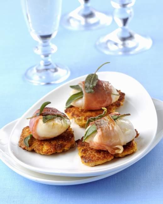 Capesante avvolte nella pancetta su una frittata di ceci su piatto bianco — Foto stock