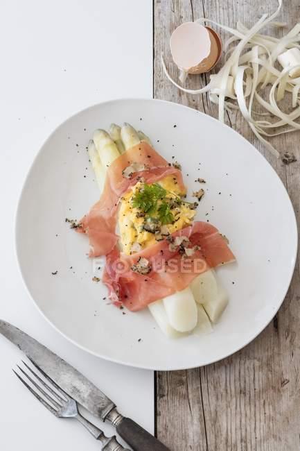 Espárragos blancos con huevo revuelto, jamón de Parma y trufas en plato blanco - foto de stock