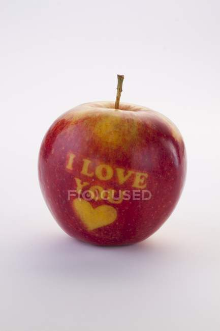Closeup view of red apple carved with the words I love you and a heart — Stock Photo