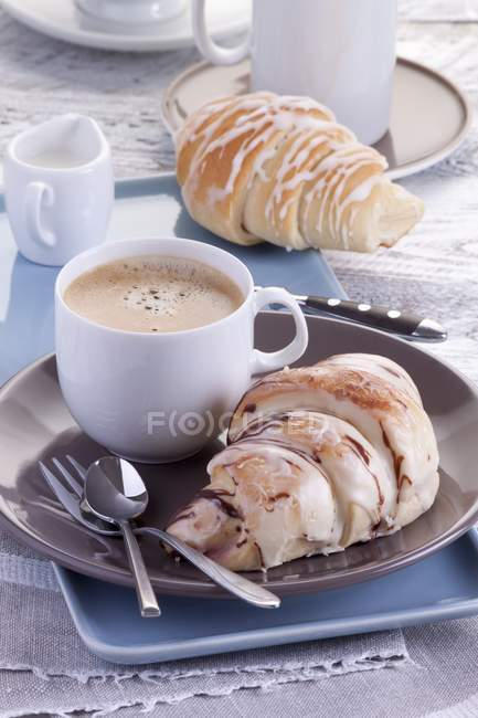 Croissants with icing and coffee — Stock Photo