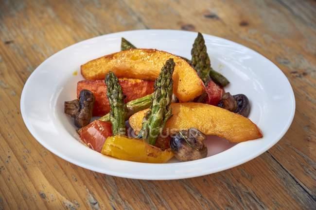 Verdure alla griglia con sale e olio d'oliva su piastra bianca su superficie in legno — Foto stock