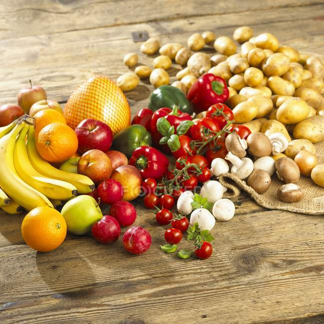 An arrangement of vegetables, mushrooms and fruit on a wooden table — Stock Photo