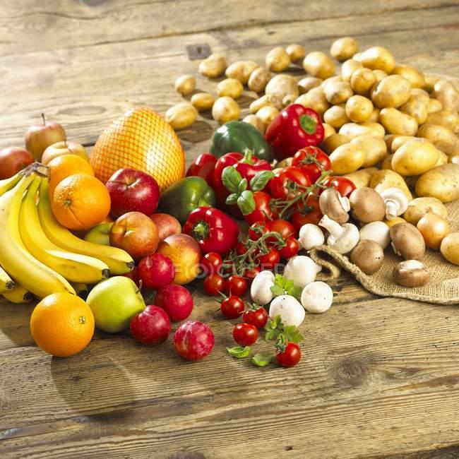 Размещение овощей, грибов и фруктов на деревянном столе — стоковое фото