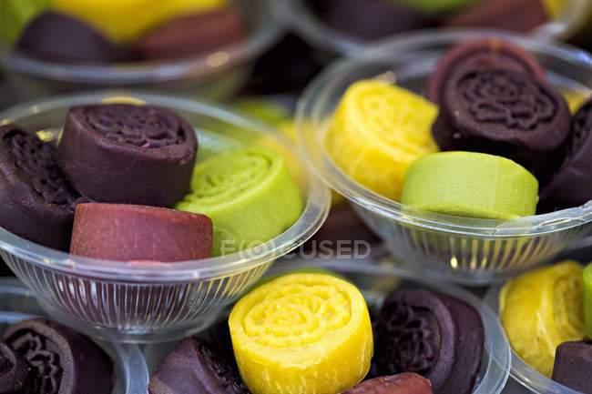 Primo piano vista di dolci colorati in ciotole di plastica — Foto stock