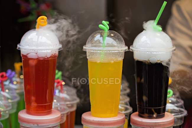 Closeup view of colored soft drinks in plastic cups on a market stand — Stock Photo