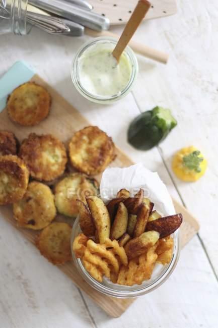 Martoriato fette di zucchine, spicchi di patate e patate della grata con un tuffo su superficie di legno — Foto stock
