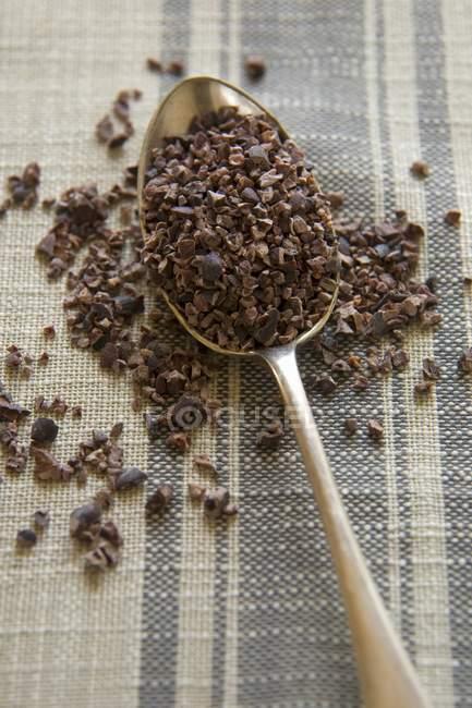 Vista superior de cerca de semillas de cacao en una cuchara - foto de stock