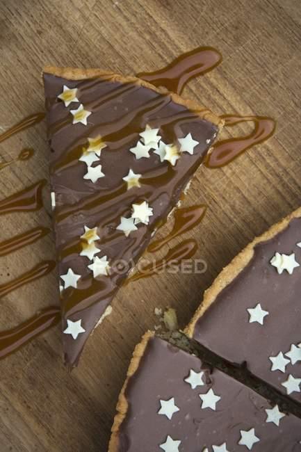 Vista superior de cerca de Tarte au chocolat decorado con pequeñas estrellas blancas y salsa de caramelo sobre una plancha de madera - foto de stock