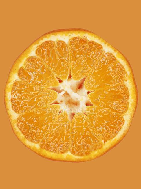 Кусочек мандарина на оранжевой поверхности — стоковое фото