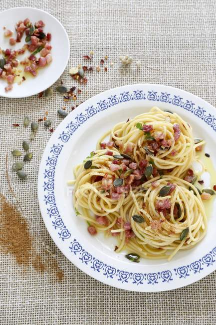 Spaghetti pasta with Pancetta and pumpkin seeds — Stock Photo