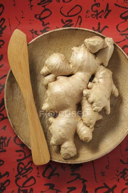 Racines de gingembre frais sur assiette en bois — Photo de stock