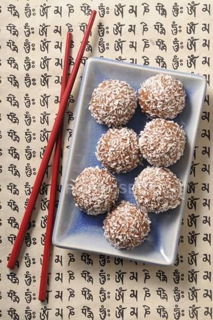 Vista superior de las bolas de coco con coco rallado - foto de stock