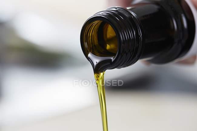 Vista del primo piano di versare olio di semi di lino da una bottiglia — Foto stock