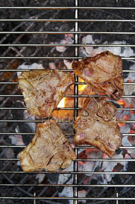 Lamb steaks on barbecue — Stock Photo