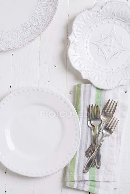 Top view of three different white plates and silver cutlery on a fabric napkin — Stock Photo