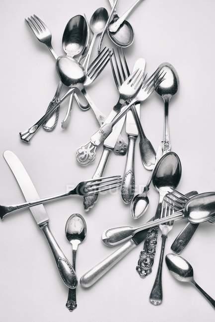 Vista superior de varios tenedores, cuchillos y cucharas sobre una superficie blanca - foto de stock