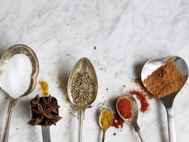 Closeup top view of spoons with assorted spices on a marble surface — Stock Photo
