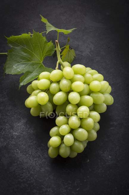 Green grapes on a black surface — Stock Photo