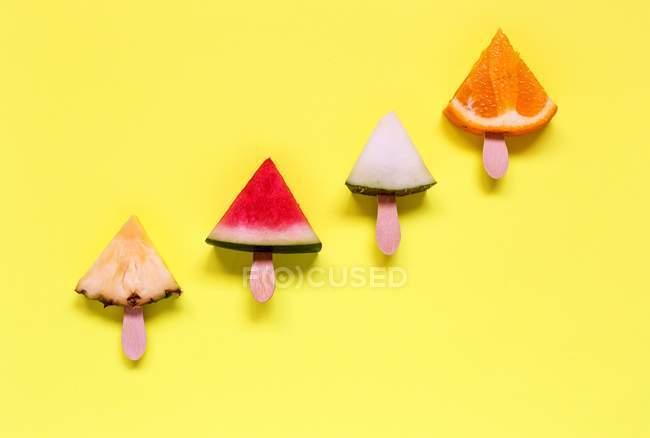 Vista close-up de vários frutos fatiados em paus em uma superfície amarela — Fotografia de Stock