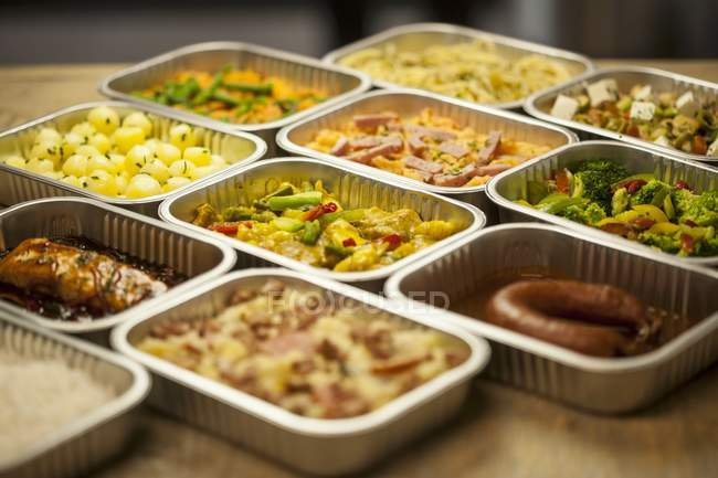 Elevated view of assorted ready meals in aluminium containers — Stock Photo