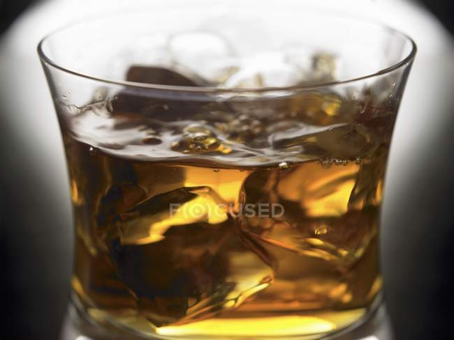 Closeup view of Bourbon with ice cubes in glass — Stock Photo