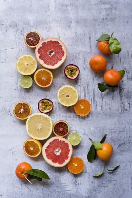 Вид сверху на различные виды нарезанных экзотических фруктов с цельными апельсинами и листьями — стоковое фото