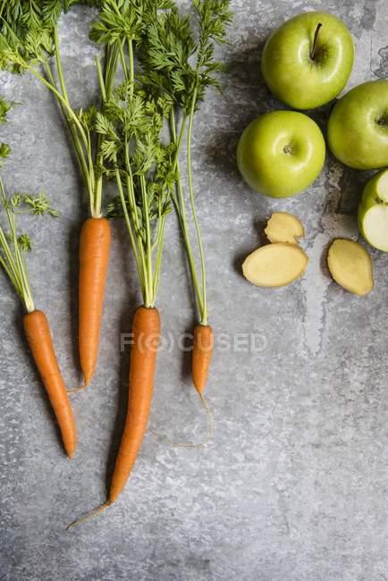 Fresh carrots on grey — Stock Photo