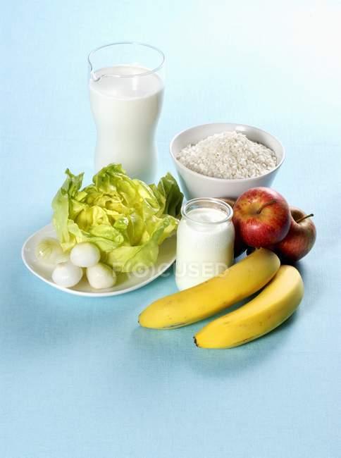 Расположение фруктов, овощей и молочных продуктов на синей поверхности — стоковое фото