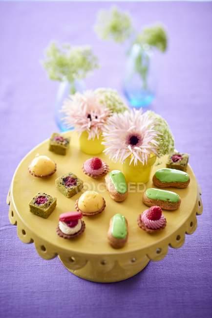 Vista ravvicinata di pasticcini e quattro petits con fiori sullo stand — Foto stock