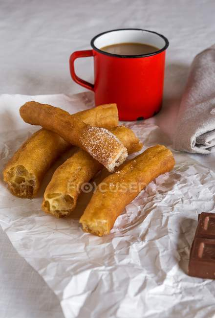 Closeup view of Churros and coffee on creased paper — Stock Photo