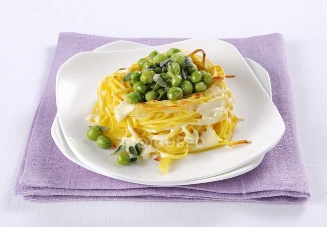 Запечена спагетті гніздяться з сиром і горох — стокове фото