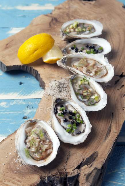 Fresh oysters with lemon slices — Stock Photo