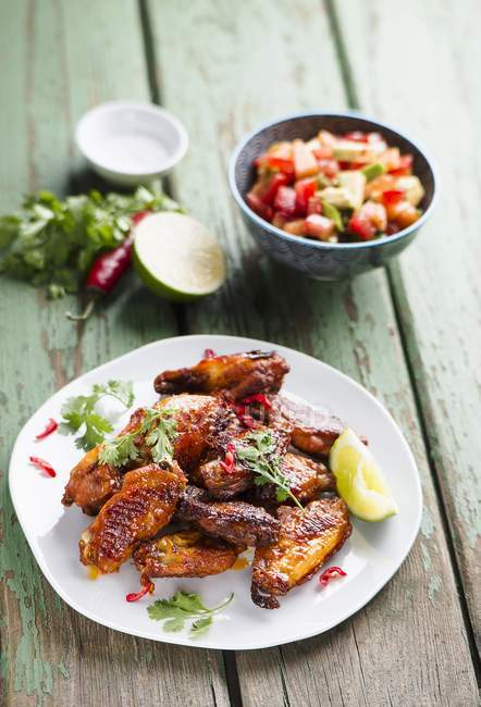Chicken wings with avocado salsa on white plate  over wooden surface — Stock Photo