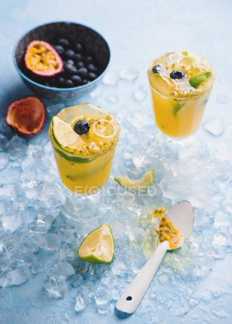 Closeup view of orange drinks with passionfruit, lime and blueberries — Stock Photo