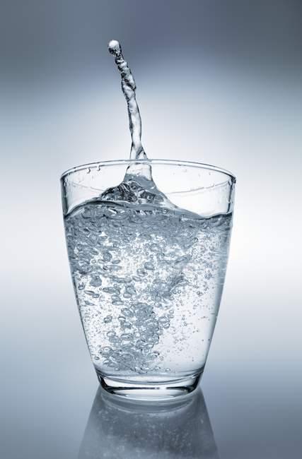 Vista del primo piano di vetro di acqua con una spruzzata — Foto stock