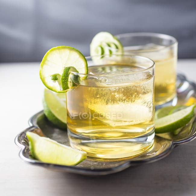 Cocktail with limes and cubes — Stock Photo