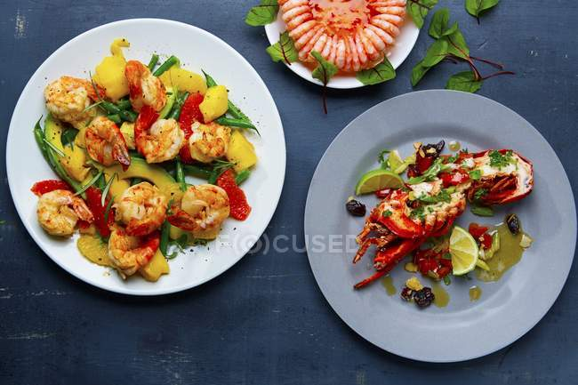 Tres platos de crustáceos: gambas con fruta, un anillo de gambas en medio de langosta - foto de stock