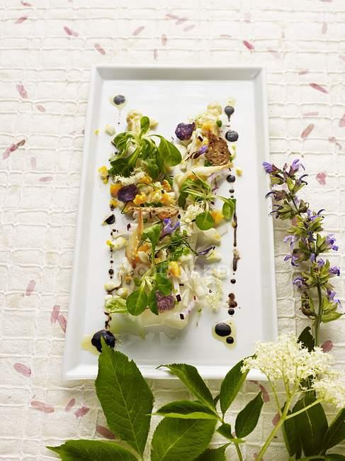 Tiepidi asparagi marinati con ravanelli, uova e fiori di sambuco sulla zolla bianca sulla superficie di legno — Foto stock