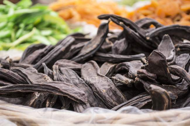 Closeup view of dry carob pods in a basket — Stock Photo