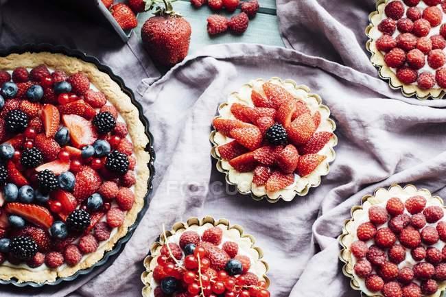 Closeup view of various berry tarts on cloth — Stock Photo
