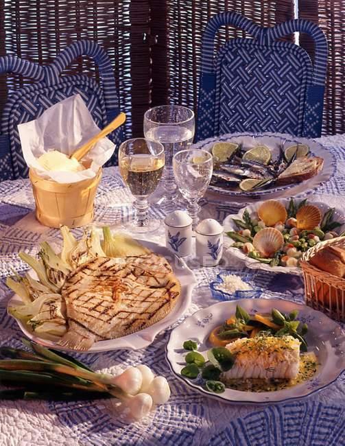 Vista diurna del bacalao con vieiras y brill sobre una mesa colocada - foto de stock