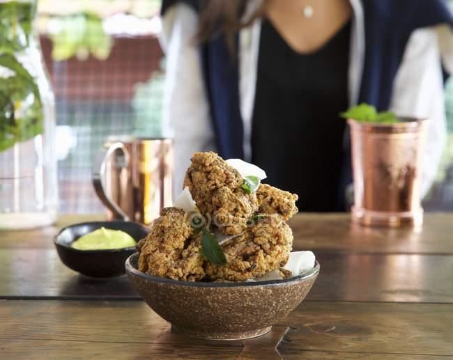 Крупным планом вид хрустящая жареная курица с травы и женщина на фоне — стоковое фото