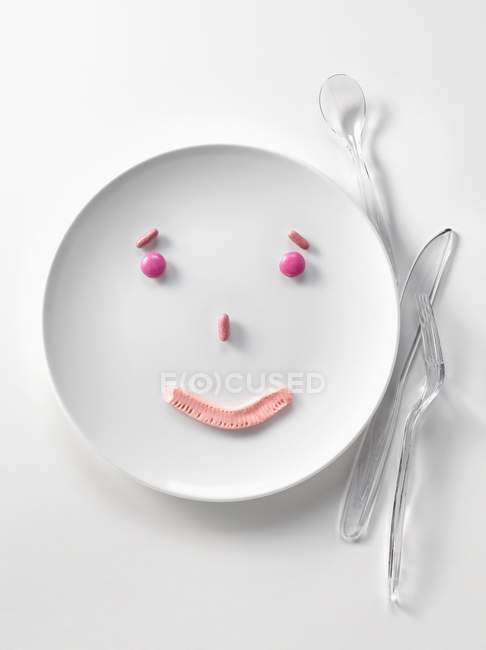 Closeup view of pink candies in shape of smiling face on white plate — Stock Photo