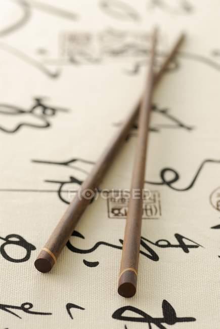 Vista de cerca de dos palillos chinos sobre papel con escritos - foto de stock