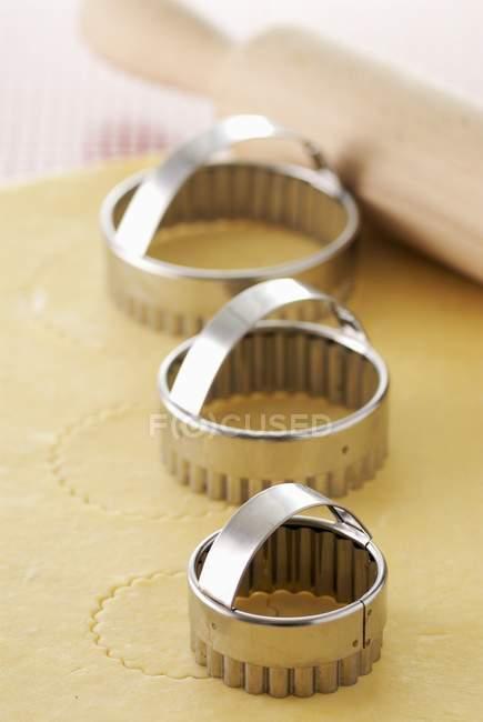 Closeup vista três cortadores de biscoito com rolo na massa — Fotografia de Stock