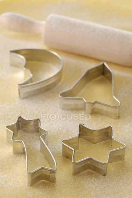 Closeup vista de diferente forma de cortadores de biscoito e o rolo na massa — Fotografia de Stock
